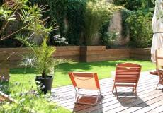 Jardin structuré par un muret de soutènement, un espace gazon et une terrasse en bois exotique, Sceaux