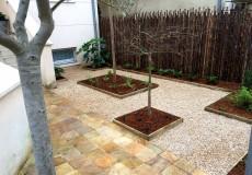 Aménagement composé de massifs bordés de volige bois, sol en nids à gravier et clôturé de bambous noirs