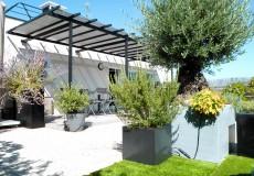 Plancher composite gris, végétation méditerranéenne, toile d'ombrage sur pergola, gazon synthétique pour l'espace enfant, Issy-les-Moulineaux