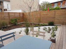 Jardinet comprenant terrasse bois, plantations et paillage