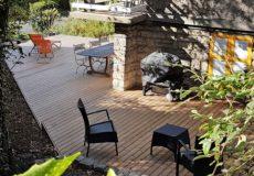 Terrasse permettant d'accueillir une grande table, un barbecue, et un espace détente.