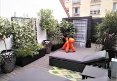 Terrasse en composite gris agrémenter de bac en émail noir et plantes grimpantes à Paris