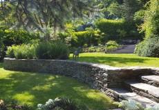 Réalisation d'une retenue en pierres sèches dans un jardin spacieux et arboré